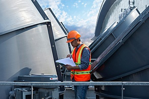 man servicing cooling tower on building