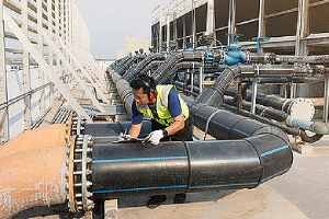 Engineer inspects cooling tower operations. Ensure that your cooling towers are not harboring Legionella bacteria
