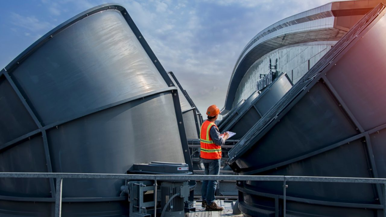 Expert conducting Legionella testing at an industrial cooling tower