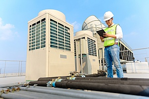 an employee of a Legionella testing company working on a cooling tower